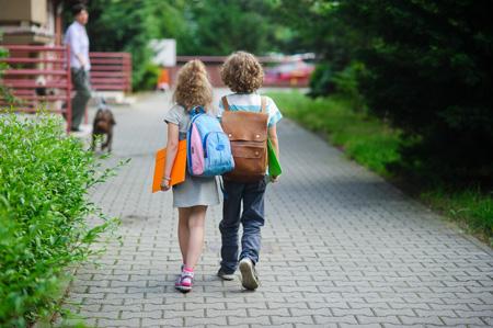 children with backpacks walking to school